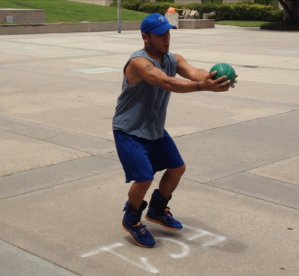 client Teddy C. training with heavy ball and ankle weight